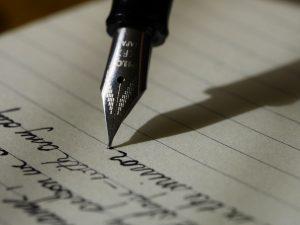 A fountain pen writing cursive text on a legal pad.