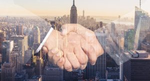 Business handshake with a soft focus cityscape in the background.