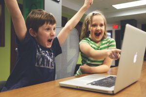 Two children cheering and pointing at a laptop screen