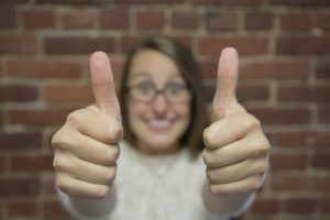 A woman standing in front of a brick wall, holding 2 thumbs up to the camera.
