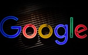 A neon sign of the Google logo against a corrugated metal background.