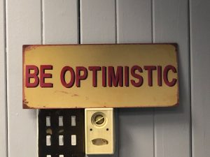A gold sign, with 'Be Optimistic' written in red font.