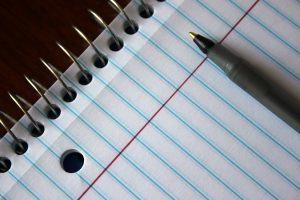 A pen sat atop a blue ruled notebook, both on a wooden surface.