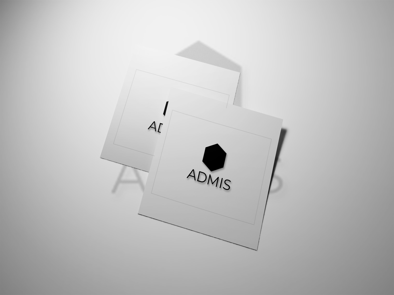 A image of two pieces of white paper with both of them displaying the Admis Logo which is black