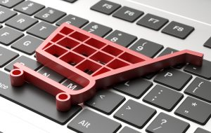 A pink plastic shopping cart laying atop a laptop keyboard.