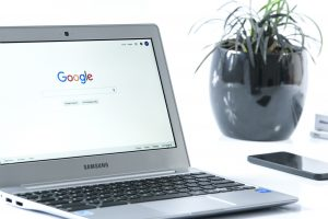 A white laptop on a white table showing the Google homepage. A potted plant in the background.