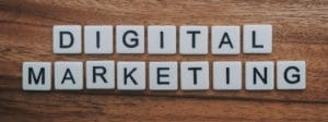Scrabble tiles on a wooden surface, arranged to spell 'Digital Marketing'