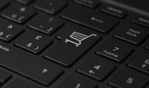A close-up of the enter key on a black keyboard, the word 'Enter' having been replaced with a shopping cart icon.