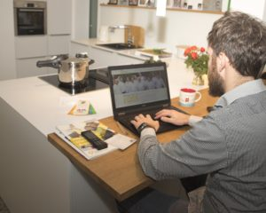 Man working on a laptop in his kitchen
