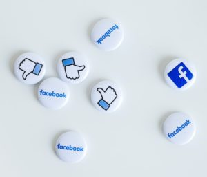 White and blue buttons featuring facebook logos and the 'like' icon scattered on a white surface