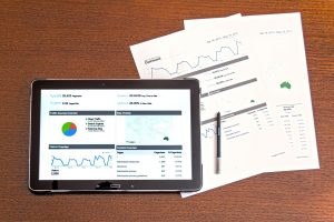 A Tablet computer showing an analytics screen and a printed analytics report both resting on a wooden surface.