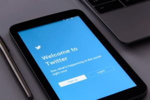 Close up of a black smartphone on a grey desk, next to a brushed steel laptop, the phone is displaying the Twitter sign up page.