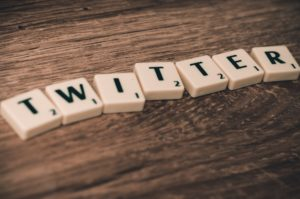 the word 'Twitter' spelled out using Scrabble tiles on a wooden surface.