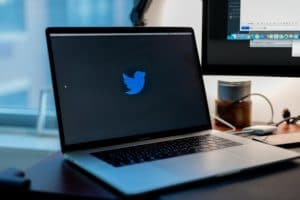 A MacBook on a modern wooden desk, displaying the Twitter logo in the center of the screen, against a black background