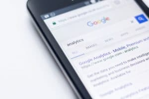 A smartphone on a white surface, a google results page for the term 'analytics' visible on screen.