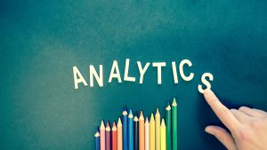 The word analytics spelled out in sign lettering on a green background, coloured pencils below the word imitating the shape of a line graph trending upwards. A finger can be seen in the bottom-right corner pushing the 'S' into place.