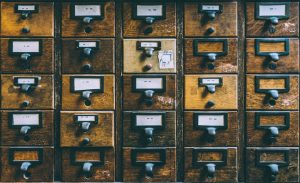 25 Vintage wooden mailboxes arranged in a 5-by-5 square. their front panels each a slightly different shade of brown.