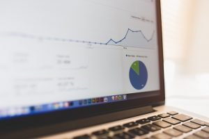 A close up of a laptop screen, showing a line graph and a pie chart in sharp focus.
