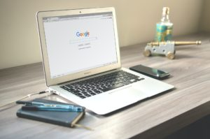 A laptop sat on a modern wooden desk, a smartphone, notebook and pens on either side of it. On the screen is shown the Google Homepage