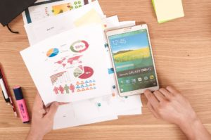 While sat at a desk, a person holds a bundle of analytics reports in one hand, while reaching for their smartphone with the other.