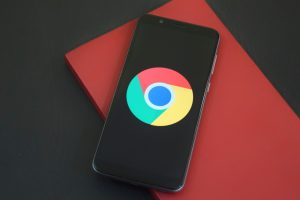 a black smartphone displaying the Google Chrome logo fullscreen, on a red and black background