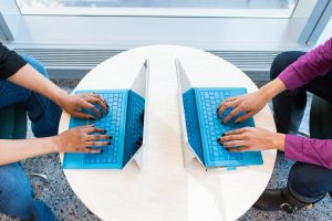 2 People facing each other using laptops with bright blue keyboards n a light-coloured wooden surface.,