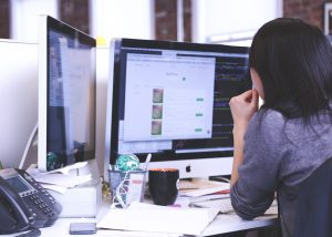 woman looking pensively at the dual-monitor IT workstation on her desk.