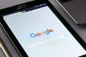The Google homepage displayed on a smartphone, the phone sat on a grey, possibly metallic surface