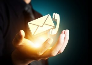 A hand holding an envelope icon and a phone icon, both icons floating above a bright yellow glow, like sunlight.