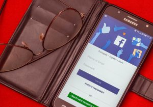 A Smartphone showing the Facebook signup page, in an open brown book-style case with an upturned pair of glasses resting on the visible side of the case. All of this is on a red surface.