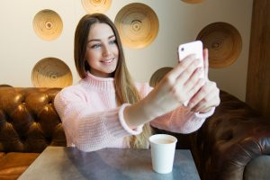 A Woman sat at a table, smiling and holding her phone out in front of her as if taking a selfie.