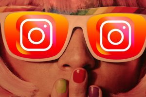 close up of a woman with her hand covering her mouth, the lenses of her glasses replaced with the Instagram logo.