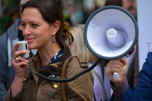 smiling woman speaking into a handset attached to a megaphone.