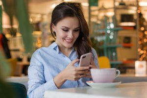 A woman sat at a table with a cup of coffee, smiling and looking at her smartphone