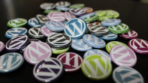pin-on buttons bearing the WordPress logo in white, with backgrounds of different colours - all on a black background