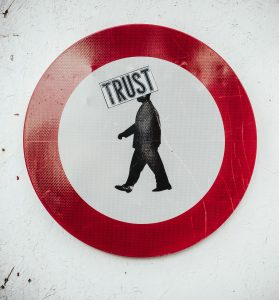 A warning-style sign with an image of a man walking in the centre, and the word 'Trust'