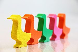5 wooden ducks in a row, each painted a different colour, standing against a white background.