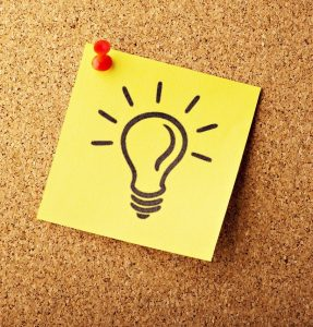 A post-it note with a light bulb drawn on it, pinned to a cork noticeboard.