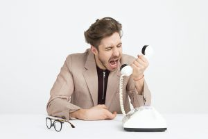 Frustrated man screaming into the handset of a rotary phone