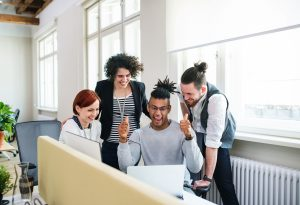 a group of young people looking at a computer screen, smiling in wonderment and success.