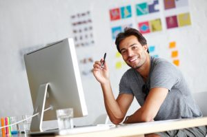 smiling man in grey t-shirt sat at a computer in a white room, smiling at the camera.