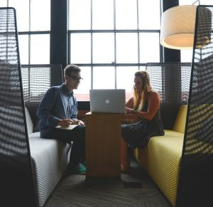 A man and woman sat at a table in a modern office setting, looking at a laptop together.