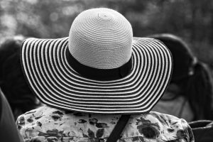 A black and white striped straw hat being worn by a woman facing away from the camera.