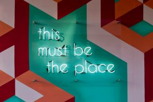 'this must be the place' written in a teal neon sign, mounted to a teal wall featuring a geometric design in red and pink