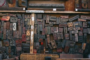 various wooden letters from an old style printing press arranged and displayed in a vintage storage tray