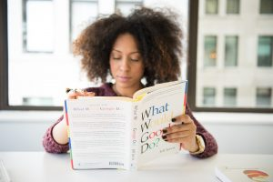 Woman sat at a desk reading a book entitled 'What Would Google Do'