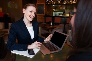 two women in business attire in a cafe, discussing business. one has an open laptop and papers with her.