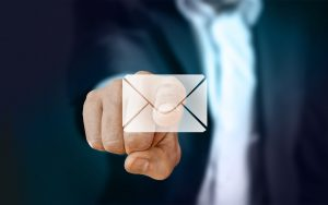 a man in a suit reaching out towards your screen, as if tapping a large envelope icon.