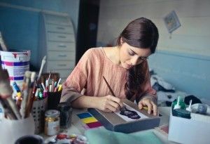 A woman looks down, concentrating as she paints into a design