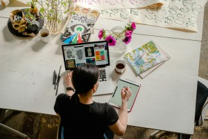 A graphic design expert working at a large table, surrounded by sketch pads, design book and a laptop